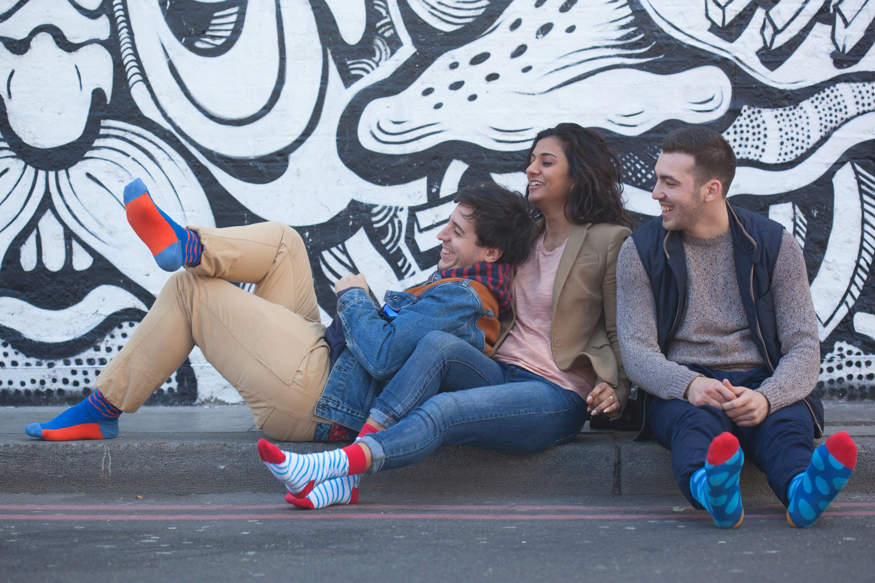 Friends wearing Lookmate socks sitting at the curb