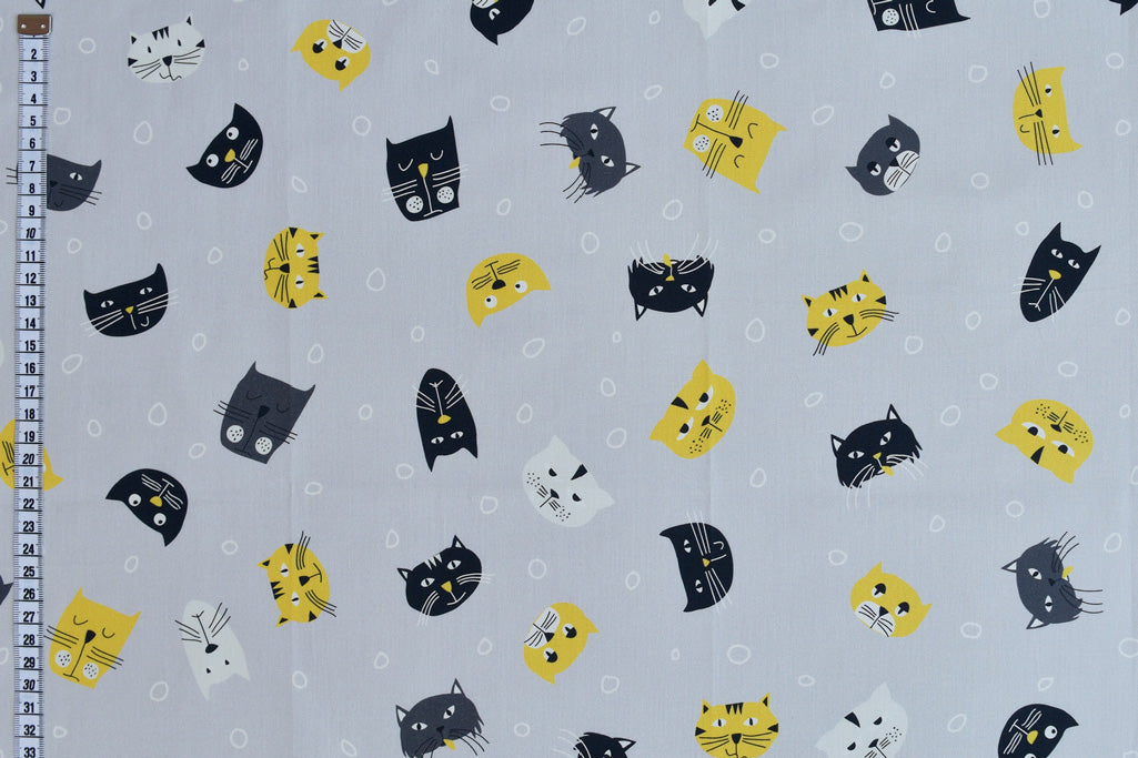Pale Blue Funky Cats - Yellow, Black & White Cat Faces on a Pale Blue Background
