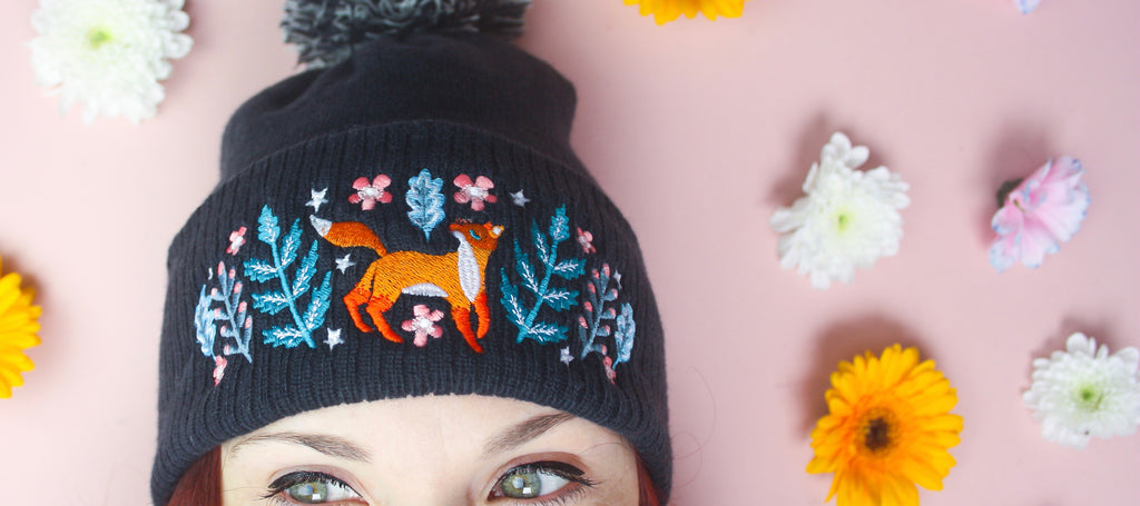 A landscape image featuring a woman wearing a navy blue beanie with a fox embroidered onto it.