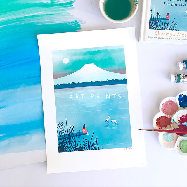 A photograph of a watercolour painting featuring a lake and Mt. Fuji with a woman dipping her toe into the lake. The image is captioned with Art Prints.