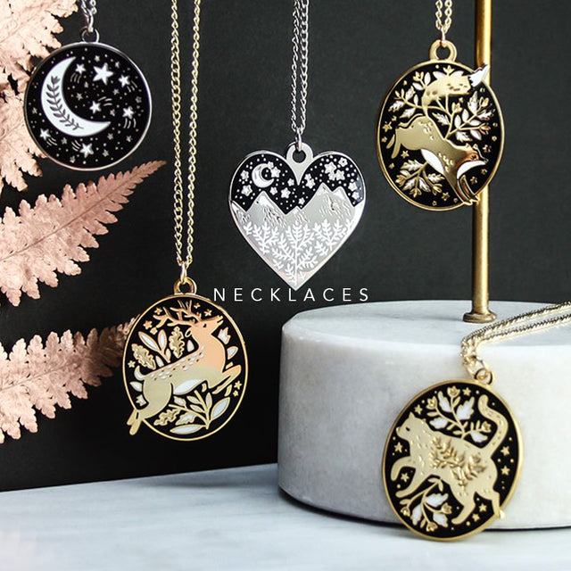 A collection of hanging necklaces on a black background. This photo features the stag, cat, fox, mountain and moon and stars necklaces. The image is captioned with Necklaces.
