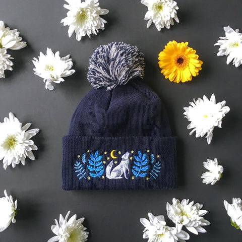A navyblue wooly hat with a blue and white bobble. The hat has a white wolf and blue florals embroidered onto it.