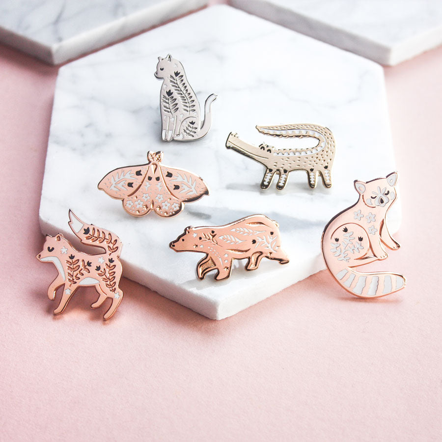A collection of enamel pins on a pink background. This photo features the cat, moth, crocodile, bear, fox and red panda pins.