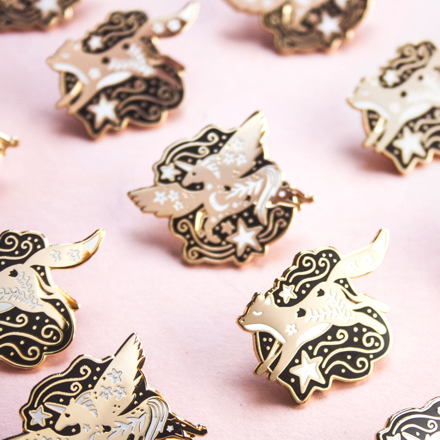 A group shot of the celestial call and celestial pegasus enamel pins.
