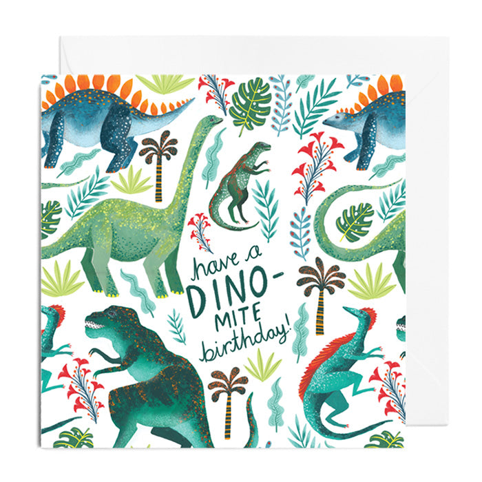 A white greetings card with green dinosaurs surrounded with florals and foliage. It's captioned with have a DINO-mite birthday!