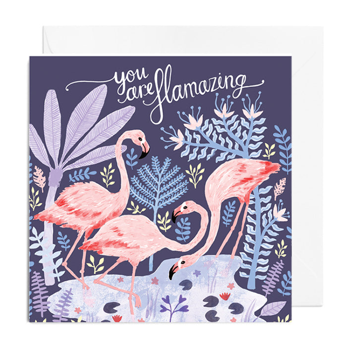 A purple greetings card featuring three flamingos drinking from a pond in a jungle. It's captioned with you are flamazing.