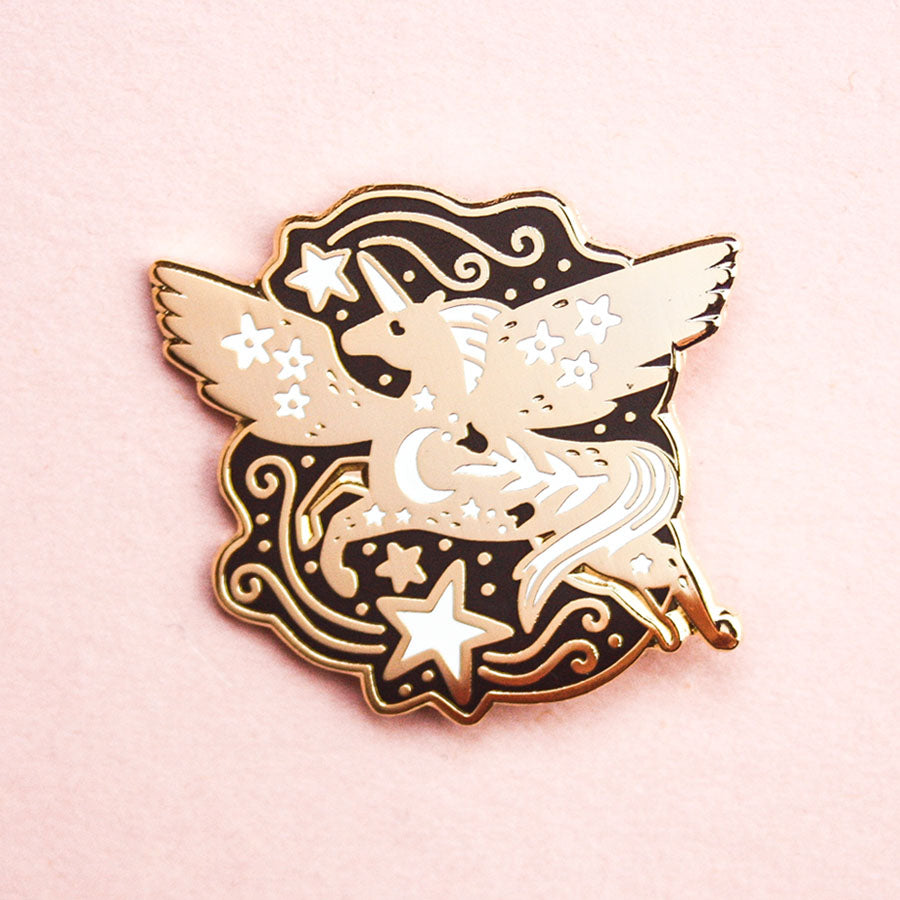 a gold enamel pin in the shape of a flying pegasus. The pegasus is surrounded by white stars and golden swirls.