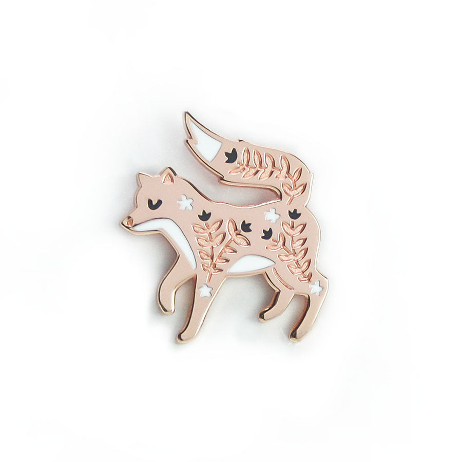 A rose gold enamel pin in the shape of a fox. The pin features engraved details in black and white.