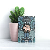The fox enamel pin on it's backing board posed in front of a cactus.