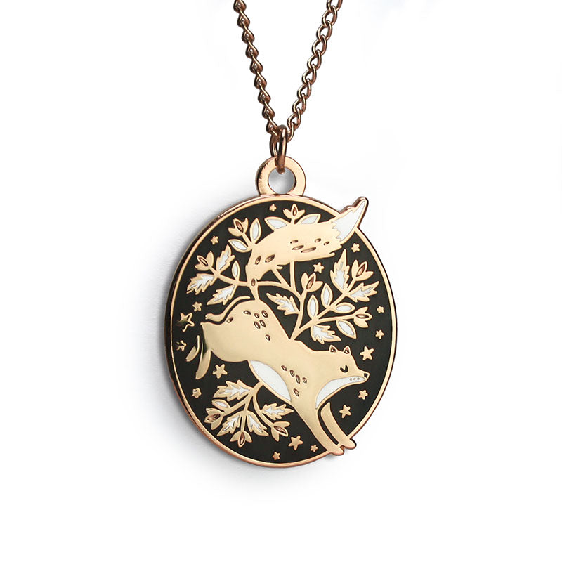 A golden oval necklace featuring a leaping fox surrounded by florals.