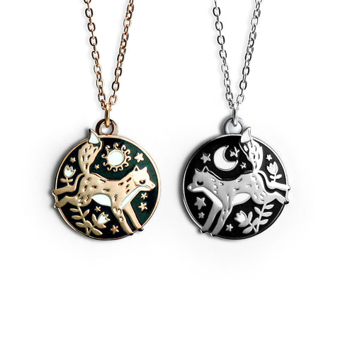 A close up of two necklaces, one gold and one silver. Each necklace features a fox and florals, one with the sun and the other with the moon.