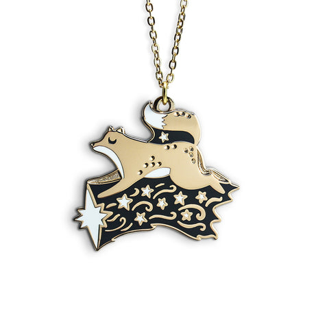 A golden necklace featuring a leaping fox above a white shooting star.