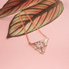 A triangular rose gold enamel necklace featuring a fox surrounded by florals, resting on a leaf on a pink background.
