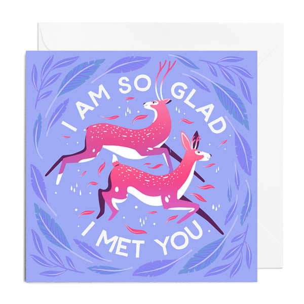 A light blue greetings card with two pink leaping deer surrounded by blue leaves. It's captioned with I AM SO GLAD I MET YOU.