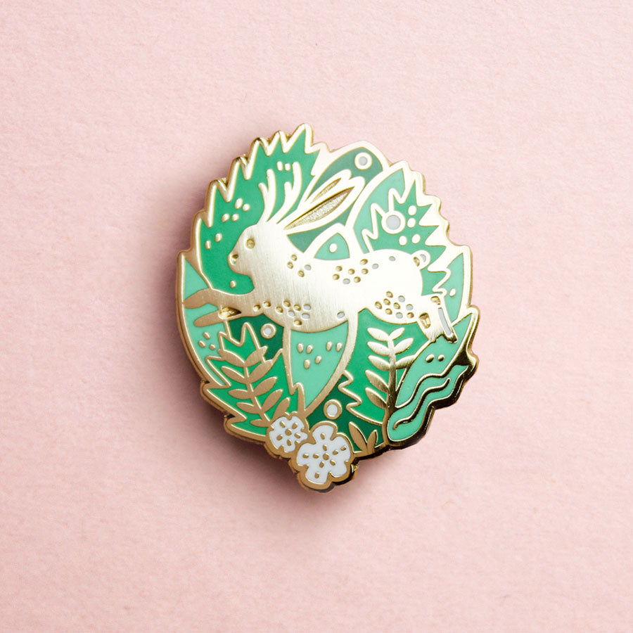 A gold enamel pin in the shape of a leaping jackalope. The jackalope is surrounded by green and gold leaves and foliage.