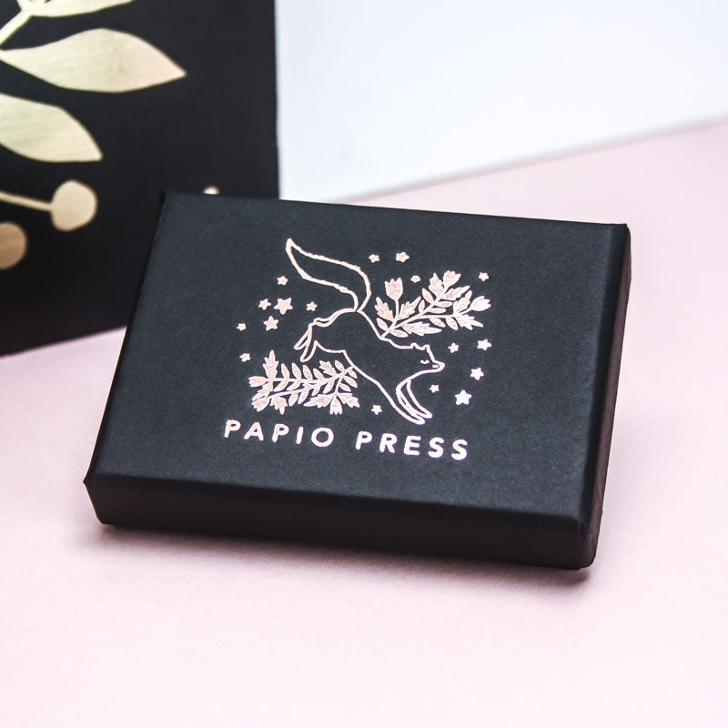 Papio Press necklace packaging. A black paper box, featuring rose gold foiling of a leaping fox surrounded by florals.