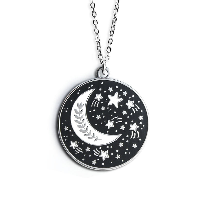 A circular silver necklace featuring a white crescent moon with a wreath inside it. Outside of the moon are white stars and swirls.