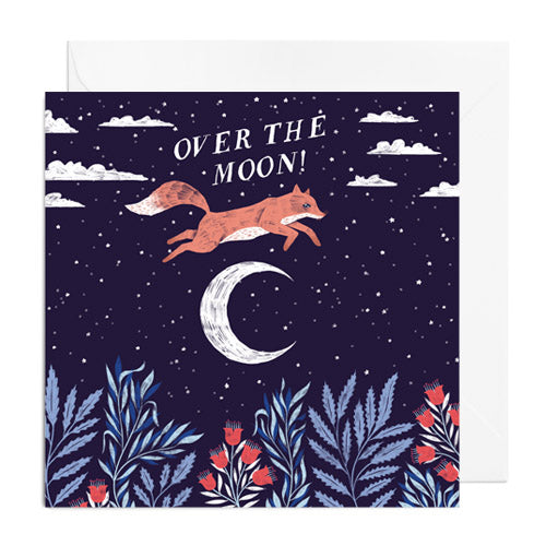 A dark blue greetings card featuring a fox leaping over a crescent moon. It's captioned with OVER THE MOON!