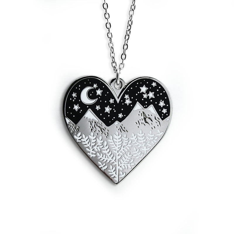 A silver heart shaped necklace. The bottom of the heart features silver snow-tipped mountains with white leaves inside it. The top of the necklace features the black sky with a white crescent moon and stars.