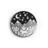 A circular silver enamel pin featuring mountains against a night sky. On the mountains in a white fox and florals.