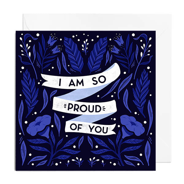 A black greetings card featuring blue florals and foliage. In the centre of the card is a banner that says I AM SO PROUD OF YOU