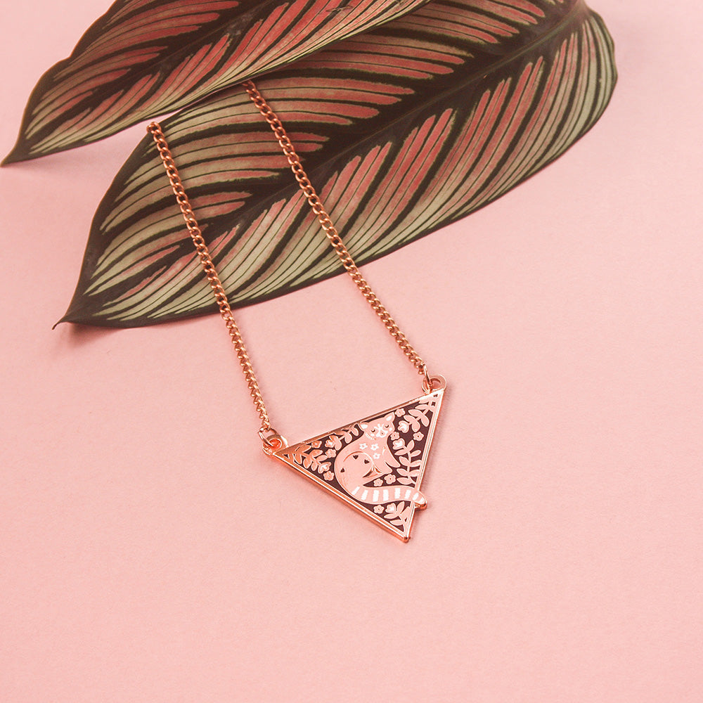 A triangular rose gold enamel necklace featuring a red panda surrounded by florals, resting on a leaf on a pink background.