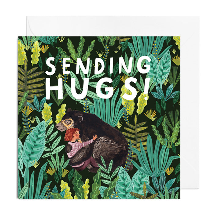 A green and black greetings card featuring a girl hugging a bear in a forest. It's captioned with SENDING HUGS!
