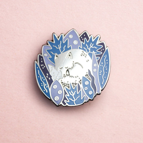 A silver enamel pin featuring a sleeping arctic fox in a bed of blue florals and leaves.