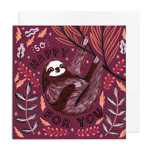 A red greetings card featuring a sloth hanging from a branch. It's captioned with so happy for you!