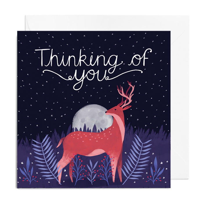 A dark blue greetings card with blue florals. It features a stag in front of a moon, and is captioned with Thinking of you.