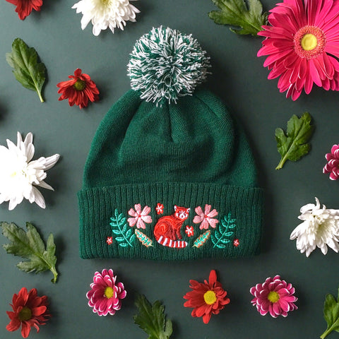 A green wooly hat with a green and white bobble. The hat has a red panda and green and pink florals embroidered onto it.