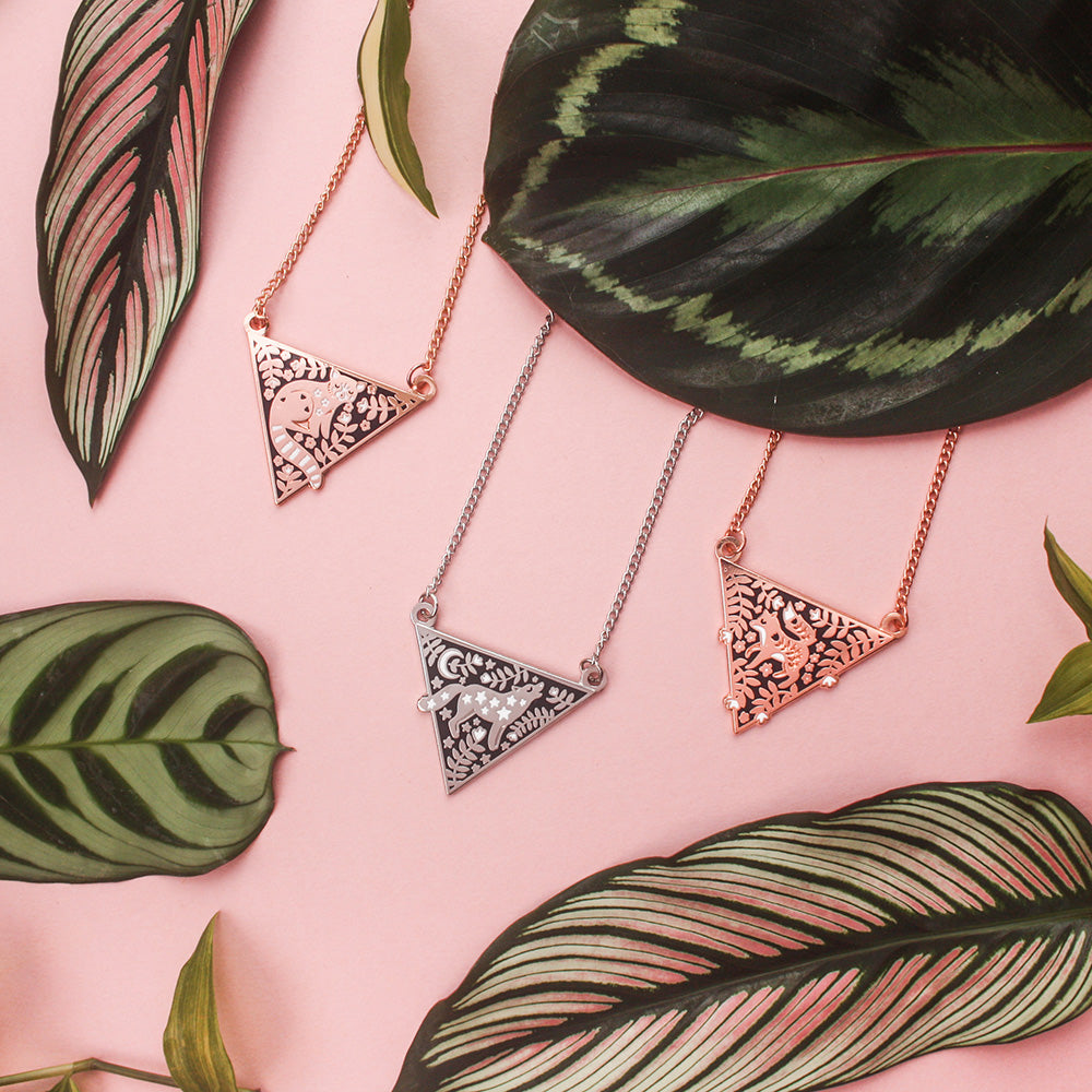 A collection of triangular necklaces surrounded by leaves, resting on a pink background.