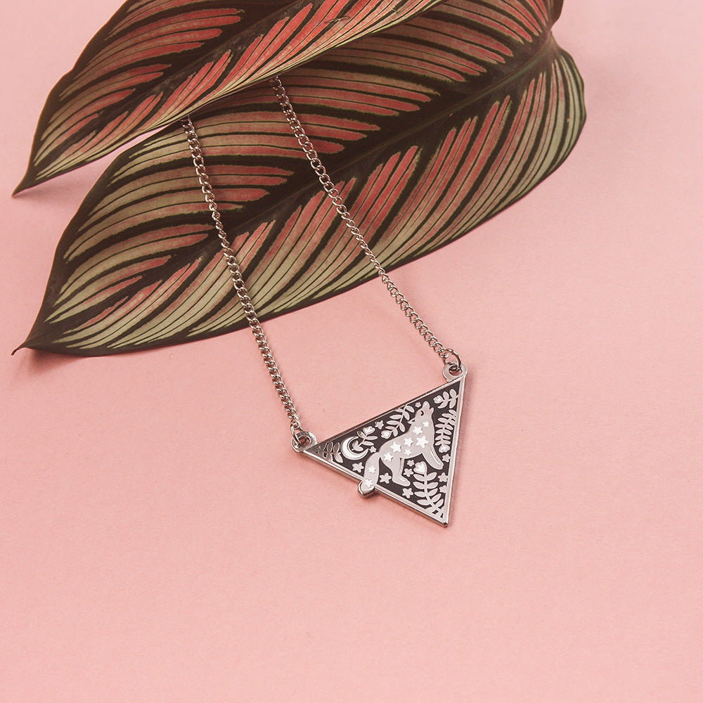 A triangular silver enamel necklace featuring a wolf surrounded by florals, resting on a leaf on a pink background.