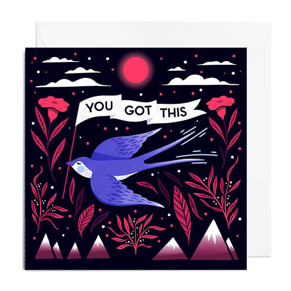 A black greetings card featuring a flying blue bird holding a banner than says YOU GOT THIS. It's surrounded by leaves, mountains and clouds.