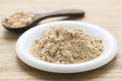 maca powder on white plate and wooden scoop