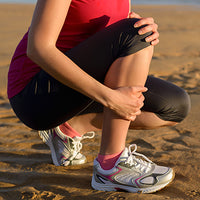 runner kneeling holding her knee and shin