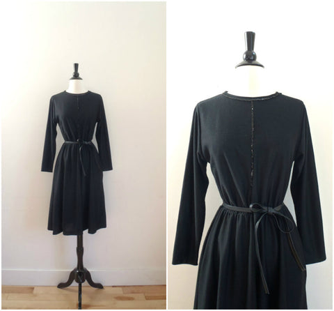 Black long sleeve dress with sequin detail and faux leather belt