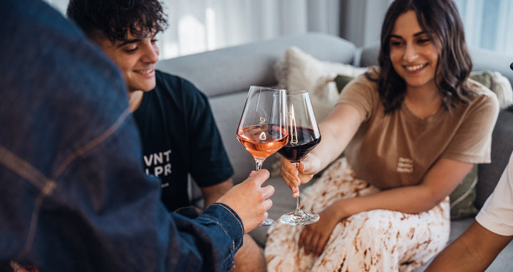 Two hands holding glasses of white wine together with a black background.