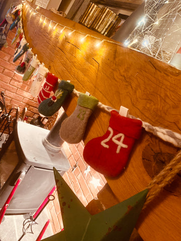 knitted advent stocking bunting hangs on a wooden fireplace
