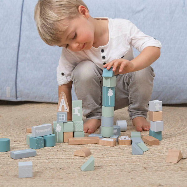 little boy builds a tower from the soft blue and aqua shade of wooden building blocks and animal shapes in a cardboard take along bucket by Little Dutch at Crane and Kind