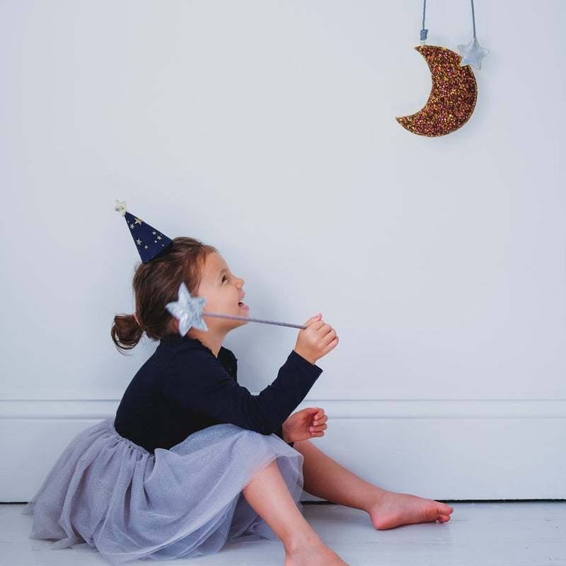 girl sits on the floor with a want and dress up hat looking at the moon in the grey sparkle gold glitter dot and gold stars tutu by Mimi and Lula and Crane and Kind
