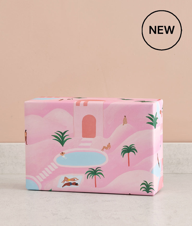 desert oasis pink luxury wrapping paper shows tranquil pools and palm trees with sunbathers perfect for a unique gift at Crane and Kind
