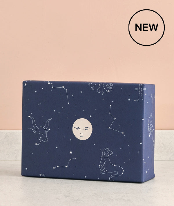 constellations on a dark blue background with stars and a stylish moon on this luxury wrapping paper at Crane and Kind for unique gifts