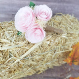 Boutonniere made with blush paper flower peonies with baby's breath, green leaves, and a burlap stem
