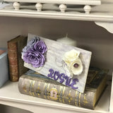 wooden personalized wall plaque made with purple glitter, paper flowers, pearls, and brooches.