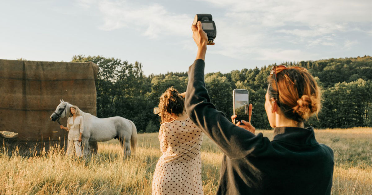 photographer using the Profoto A10 flash to light model and use with smartphone