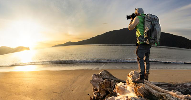 man taking photo of ocean with Think tank backpack