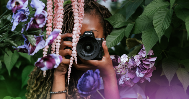 woman holding Nikon z5 surrounded by purple flowers