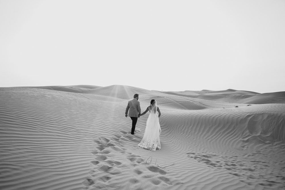 Couple holding hands and walking in sand dunes taken by mele ilikuone