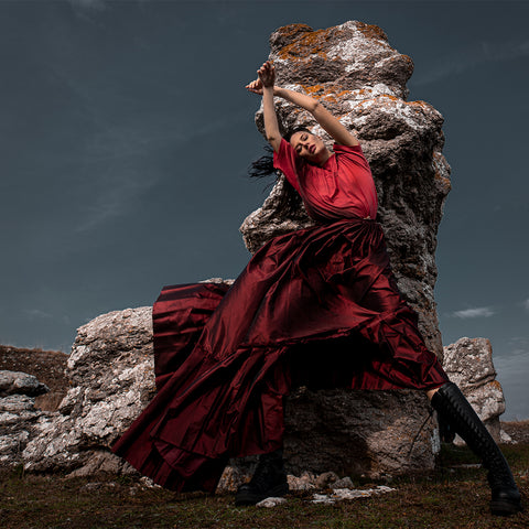 Woman in red dress, posing in front of rock